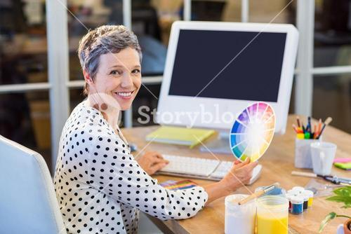 Casual businesswoman working with computer and colour chart