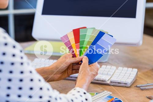 Casual businesswoman looking at colour swatch