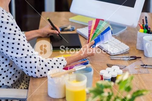 Casual businesswoman looking at colour swatch and drawing with digitizer