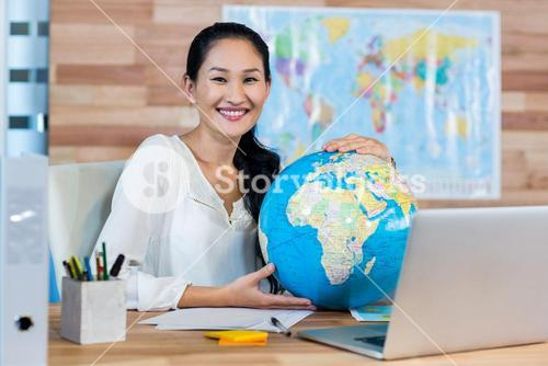 Pretty travel agent holding globe and smiling at camera