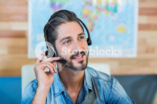 Smiling travel agent having phone call