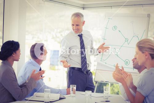 Businessman explaining the graph on the whiteboard
