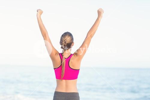Wear view of fit woman looking at the sea with arms rise
