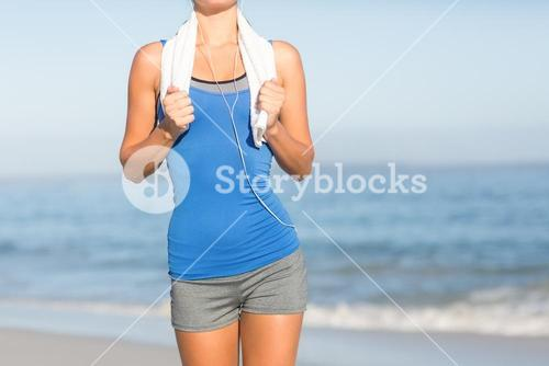 Fit woman running with towel around neck