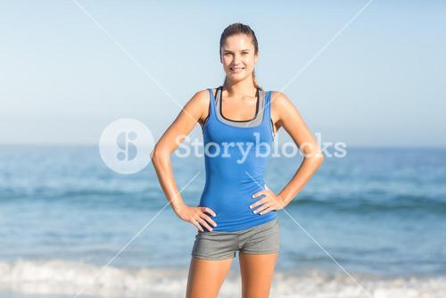 Portrait of beautiful fit woman looking at camera with hands on hips