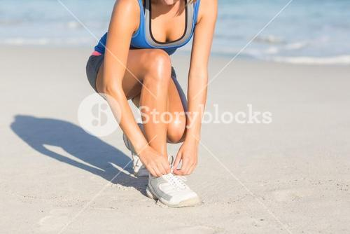 Fit woman tying her shoelace