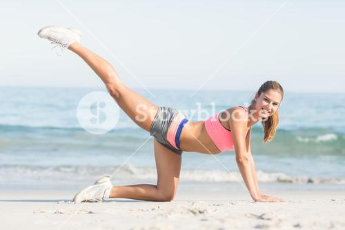 Fit woman stretching beside the sea