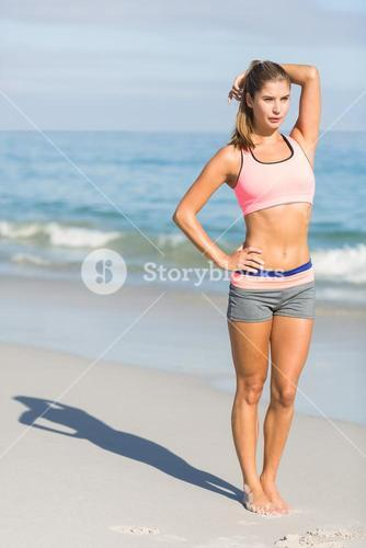 Fit woman standing beside the sea