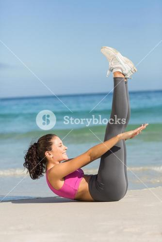 Fit woman doing fitness beside the sea