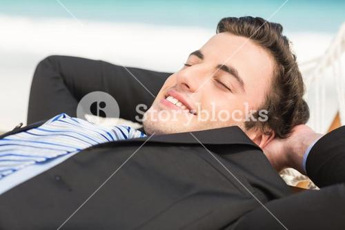 Happy businessman relaxing on the hammock