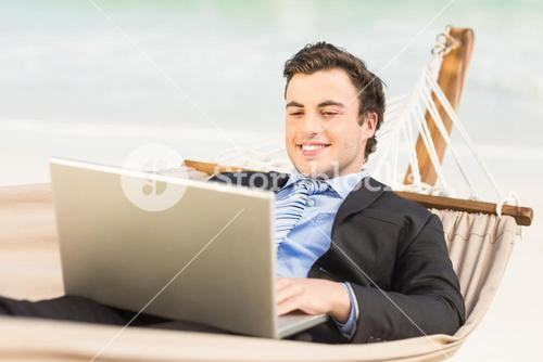 Businessman using laptop on the hammock
