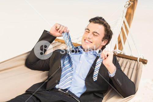 Businessman removing his tie on the hammock