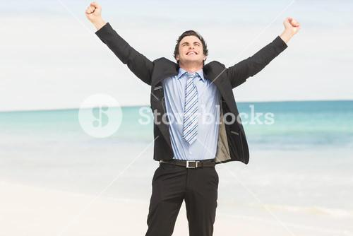 Happy businessman cheering at the beach