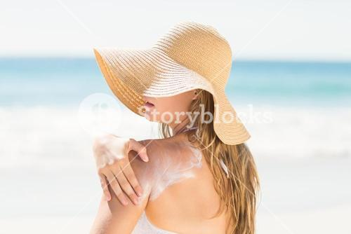 Pretty blonde woman spreading sun tan lotion on her shoulder