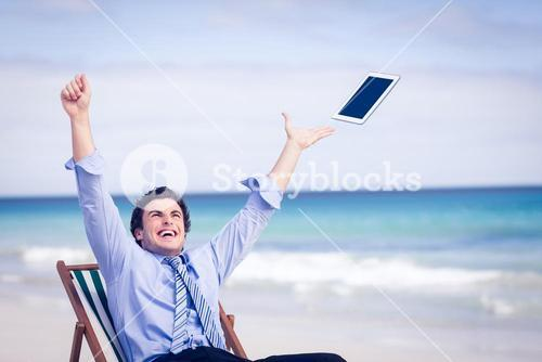 Carefree businessman throwing up his tablet in the air