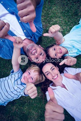 Happy family in the park gesturing thumbs up