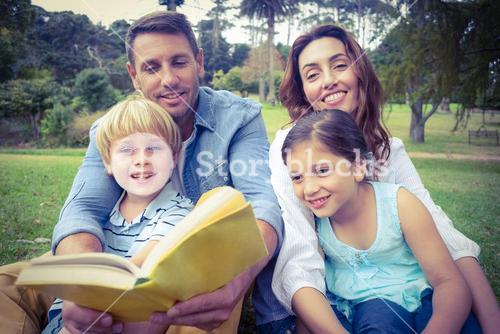 Happy familly reading a book in the park