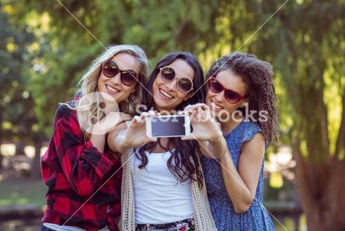 Happy hipsters taking a selfie in the park