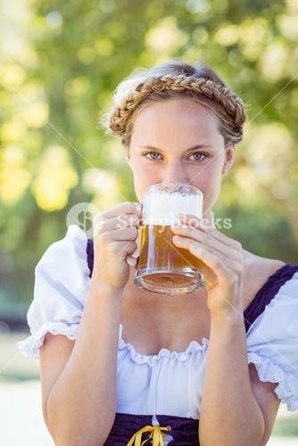 Pretty oktoberfest blonde drinking in the park