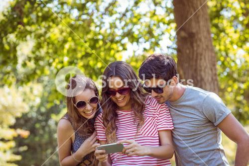 friends looking photos in a park
