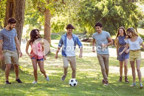 Happy friends in the park with football
