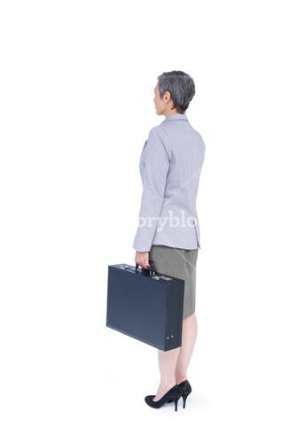 Side view of businesswoman stranding with suitcase