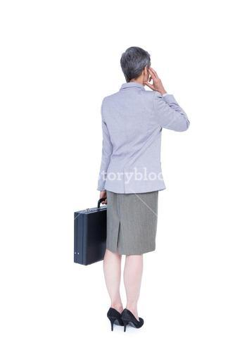 Wear view of businesswoman stranding with suitcase