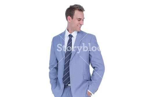 Happy handsome businessman smiling with hands on pockets
