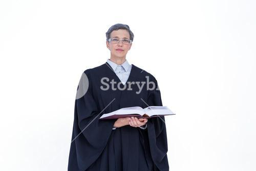 Lawyer looking at camera and holding law code