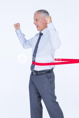 Happy businessman crossing red line