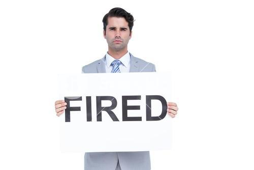 Sad businessman holding a fired sign