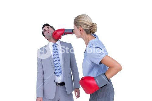 Businesswoman punching colleague with boxing gloves