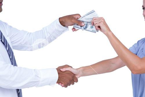 Business people shaking hands and exchanging bank notes