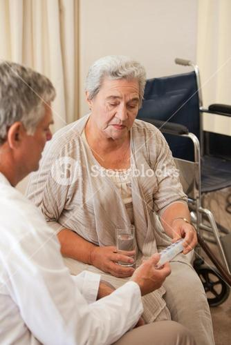 Doctor giving pills to his patient