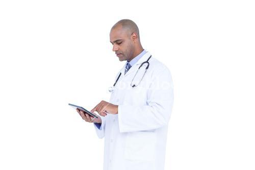 Serious doctor using tablet