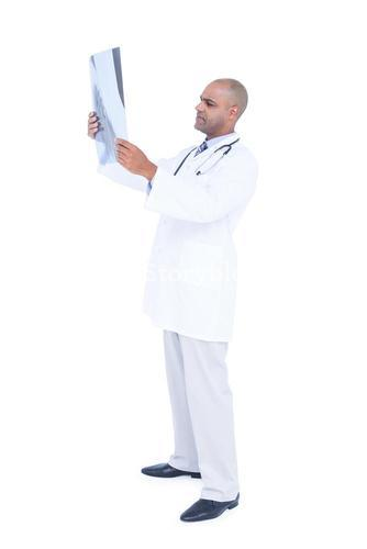 Serious doctor looking at x-ray