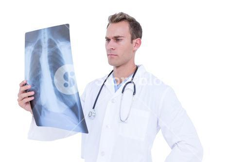 Serious young doctor looking at x-ray
