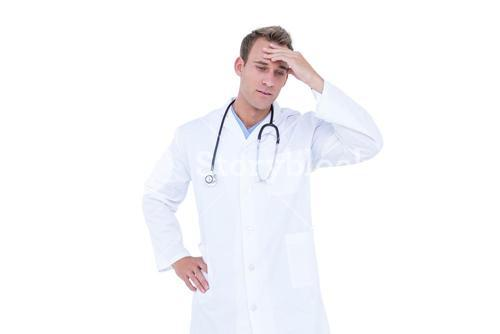 Worried young doctor in white tunic