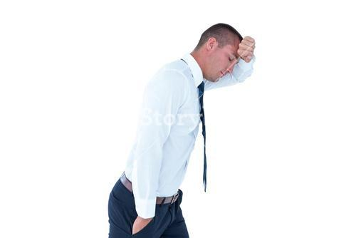 Worried businessman leaning on wall