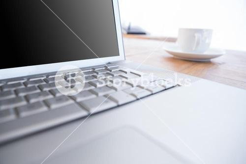 Close up of laptop and coffee on a desk