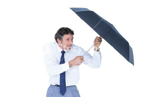 Businessman holding umbrella to protect himself