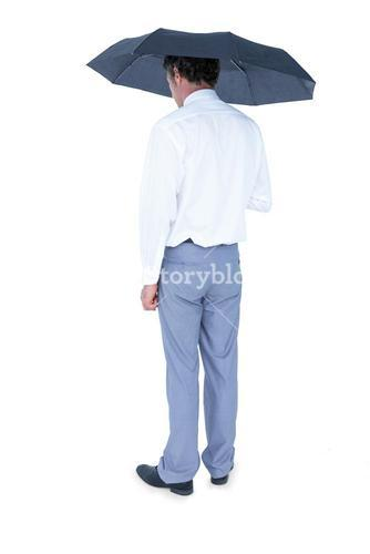Rear view of businessman holding an umbrella