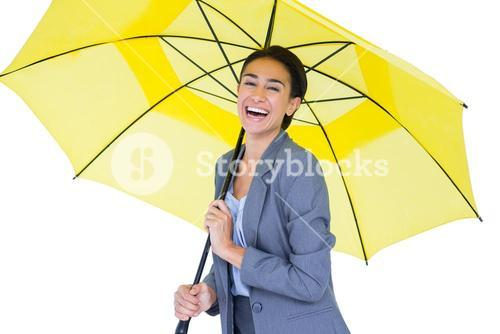 Smiling businesswoman sheltering under umbrella