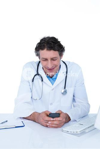 Smiling doctor texting in the office