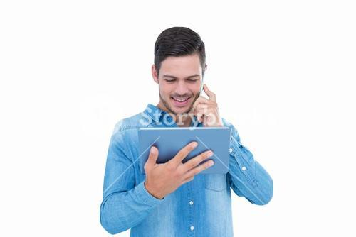 Handsome hipster on the phone holding tablet