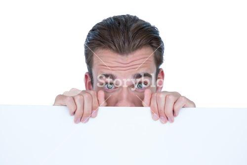 Man hiding by blank paper