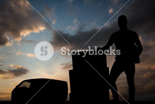 Composite image of courier man with cardboard boxes