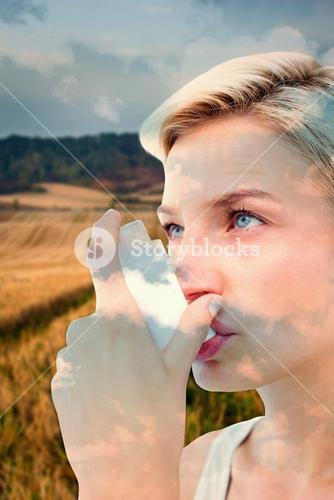 Composite image of blonde woman taking her inhaler