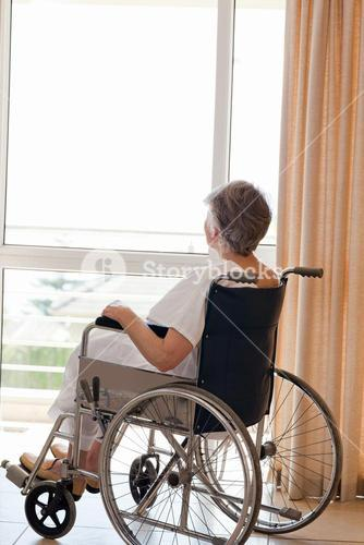 Senior woman in her wheelchair looking out the window