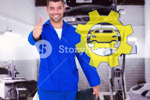 Composite image of mechanic with tire gesturing thumbs up